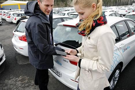 OP-ryhmän Timo Valtonen ja Sonja Heikkilä näyttävät, miten DriveNow-pavelun auto otetaan käyttöön kännykkäsovelluksen avulla. Autot lähtevät varastolta liikenteeseen kahden viikon kuluttua.