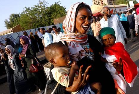 Mielenosoittaja näytti voitonmerkkiä lapset sylissään protestissa puolustusministeriön edessä huhtikuussa Khartumissa.