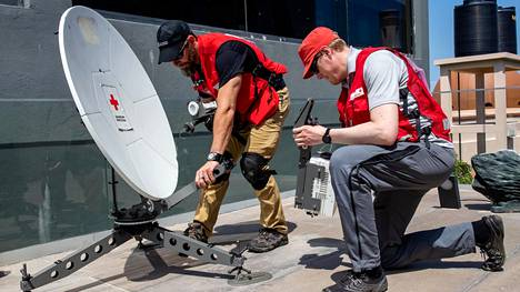 Punaisen ristin it-erikoisosaajat Jonathan Nygård (oik.) Suomesta ja Carter Stone Yhdysvalloista purkivat testaamaansa satelliittilautasta siirtääkseen sen varsinaisen asemaansa Beirassa Mosambikissa maaliskuun lopussa hirmumyrsky Idain tuhoalueella.