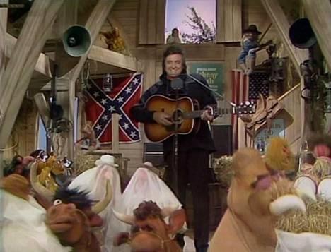 Johnny Cash esitti Muppet-hahmoille ladossa (Ghost) Riders in the Sky -kappaleen. Hänen taustallaan näkyivät Etelävaltioiden ja Yhdysvaltojen liput. Kuvakaappaus sarjasta.
