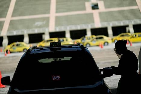 Terveydenhuollon työntekijä suorittaa koronavirustestiä taksinkuljettajille Rio de Janeirossa perjantaina.