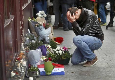Mies toi kukkia Le Carillon -ravintolan edustalle, jossa useat saivat surmansa terroristien tulituksessa perjantaina.