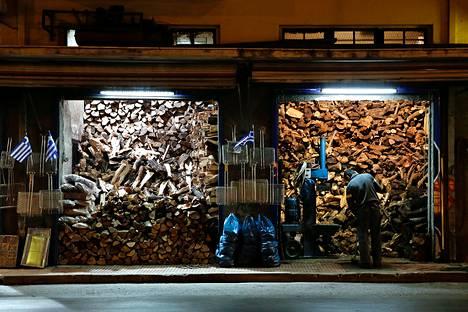 Siivooja lakaisee halkoja myyvän kaupan edustaa Ateenassa. Monet talousvaikeuksissa elävät kreikkalaiset ovat lopettaneet lämmitysöljyn käytön ja siirtyneet halvempaan, mutta saastuttavampaan puulämmitykseen.