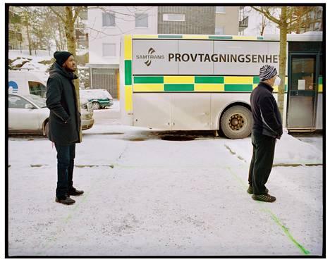 Tukholman Tenstassa koronatestejä tarjoavan bussin henkilökunta on maalannut lumeen vihreitä viivoja jonottajien turvavälejä varten.