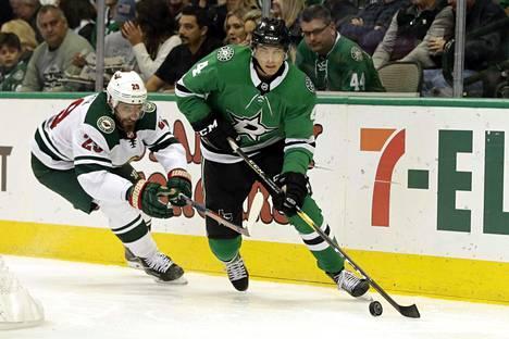 Miro Heiskanen (edessä) karkaa kiekon kanssa Minnesotan Greg Paterykta.