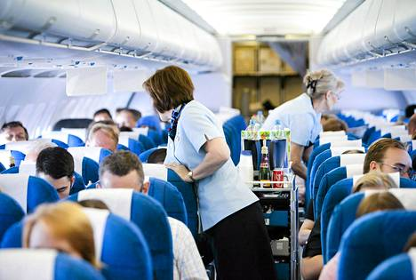 Finnairin lentoemännät palvelevat lentomatkustajia lennon aikana.