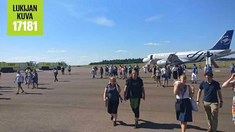 Matkustajia poistumassa savunneesta koneesta Helsinki-Vantaan lentokentällä.