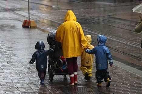 Lapset kävelivät sadevarusteissa Aleksanterinkadulla tiistaiaamuna.