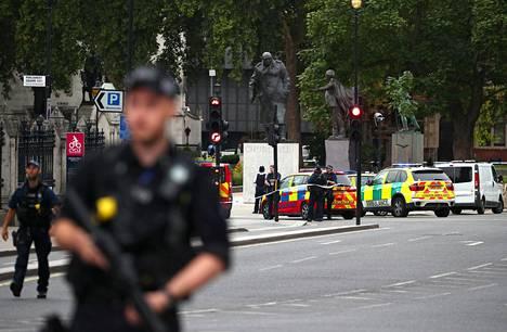 Aseistettu poliisi parlamenttitalon luona.