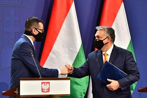 Unkarin pääministeri Viktor Orbán (oik.) ja Puolan pääministeri Mateusz Morawiecki (vas.) tervehtivät toisiaan torstaina yhteisessä tiedotustilaisuudessa Budapestissä.