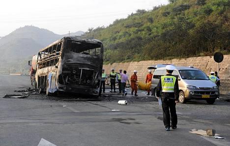 Poliisi ja pelastustyöntekijät siirsivät ruumiita palaneesta linja-autosta sunnuntaina.