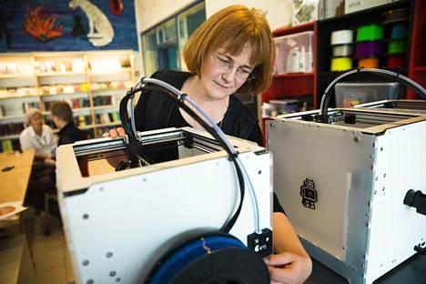 Lasten ja nuorten kirjastonhoitaja Marjukka Peltonen esittelee värjätystä maissitärkkelyksestä esineitä valmistavaa 3D-printteriä Tapiolan kirjastossa. Hänen mukaansa kirjastonhoitajan työ kehittyy, mutta ei katoa.