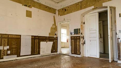 Huoneen seinistä on otettu esiin koristemaalattua rintapaneelia ja tapettikerroksia.