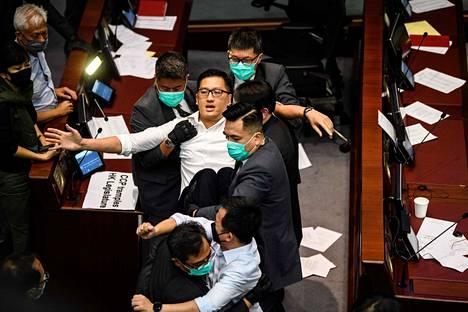 Demokratiapoliitikko Lam Cheuk-ting kannettiin ulos istuntosalista 18. toukokuuta kun kansallislaululaista tuli päättäjien keskuudessa riitaa.