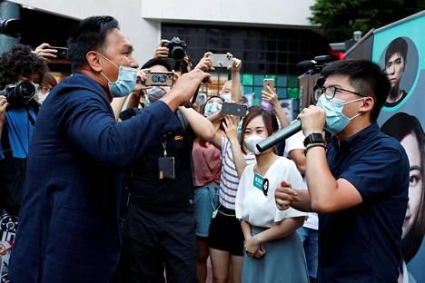 Kiinamielinen aktivisti Man Shek Fong-yau (vas.) otti yhteen demokratia-aktivistien Joshua Wongin ja Tiffany Yuen Ka-Wain kanssa opposition esivaalikampanjassa lauantaina.