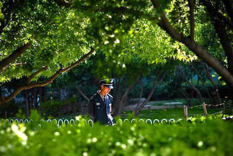 Vartija käveli puistossa ostospaikan lähistöllä Pekingissä sunnuntaina.