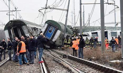 Pelastustyöntekijät seisoivat raiteilta suistuneen junan luona Pioltellossa lähellä Milanoa Italiassa.