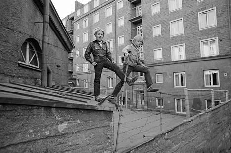 Kaksi poikaa seisomassa pihojen välisellä välipiikkilanka-aidalla Torkkelinmäessä Kalliossa keväällä 1970.