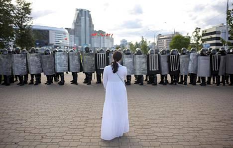 Mielenosoittaja seisoi mellakkapoliisin rivistön edessä poliisiväkivaltaa vastustaneen mielenosoituksen aikana Minskissä viime sunnuntaina.