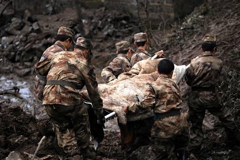Pelastustyöntekijät kuljettivat maanvyöryssä kuolleen ruumista Gaopon kylässä Lounais-Kiinassa.