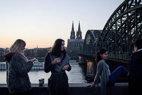Kölnissä vieraileva brasilialainen Thais Arruda (kesk.) otti talvitakin pois päältään, jotta Guillerme Vasconcellos saisi otettua paremman kuvan hänestä ja Kölnin tuomiokirkosta.