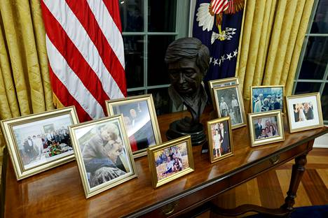 A bust of Cesar Chavez looks at Joe Biden's family photos behind a desk in the White House.