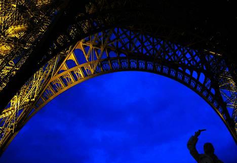 Turisti otti kuvan puhelimellaan Eiffel-tornin juurella. Ranskassa on kiellettyä julkaista ilman lupaa yöllisiä kuvia Eiffel-tornista, sillä sitä valaisevat valot nauttivat tekijänoikeuksien suojaa.