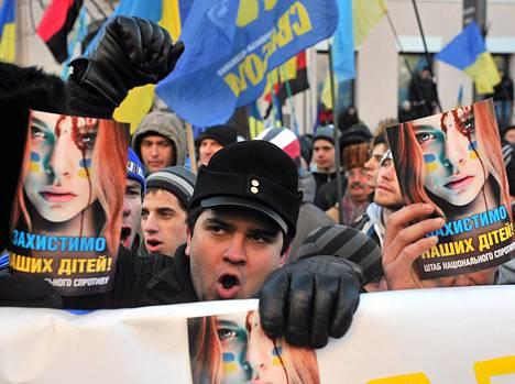 Mielenosoittajat tuomitsivat poliisiväkivallan kylteissään tiistaina.