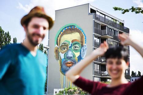 """Various (oik.) ja Gould (vas.) eli taiteilijaduo Various&Gould tekevät taidetta yhdessä Berliinissä. Heidän suuri muraalinsa Face-Time sijaitsee entisen tarkastuspisteen kohdalla Kreuzbergin ja Mitten kaupunginosien rajalla.""""Joku luuli, että maalauksessa on Obama. Se oli hauskaa"""", Gould sanoo. """"Monet myös miettivät, onko kuvassa mies vai nainen"""", Various kertoo. Pari haluaa pysyä nimettömänä."""
