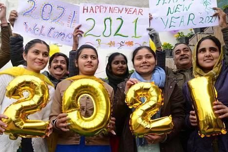 Ihmiset pitelivät numeropalloja ja kylttejä Amritsarissa Intiassa.