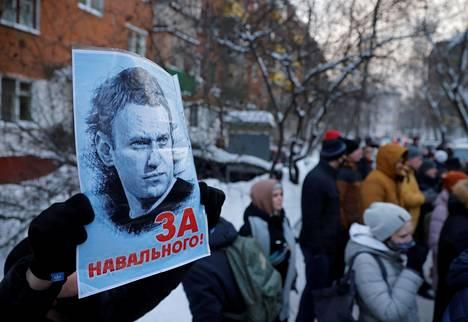 """Navalnyin säätiön julkaiseman videon jälkeen ihmiset ovat kannustaneet toisiaan jalkautumaan kaduille viikonloppuna. Navalnyin kannattaja piteli maanantaina Moskovassa kylttiä, jossa lukee """"Navalnyin puolesta""""."""
