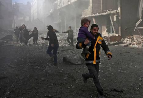 Syyrialaismies kantoi pommin tuhoaman talon rauniosta selvinnyttä lasta kapinallisten hallitsemassa Hamouriassa Itä-Ghoutan alueella maanantaina.