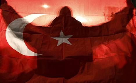 Mielenosoittaja pitelee Turkin lippua Hollannin Rotterdamissa lauantaina. Presidentti Recep Tayyip Erdoğanin kannattajat toivottivat tervetulleeksi kaupunkiin maateitse matkanneen Turkin perheministeri Fatma Betul Sayan Kayan.