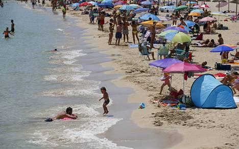 Ihmiset nauttivat auringosta Mallorcalla Espanjassa viime lauantaina, jolloin Britannia päätti palauttaa 14 päivän karanteenisäännön Espanjasta palaaville matkustajille maan kasvavien tartuntalukujen takia.