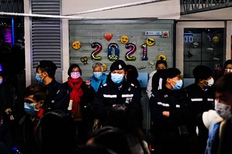 Ihmiset kokoontuivat Honkongissa juhlimaan uuttavuotta Victoria Harbouriin. Koska koronarajoitukset ovat edelleen voimassa, ilotulitukset ja muut tapahtumat oli peruttu.