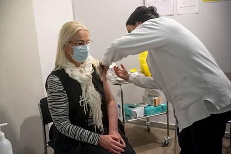 Johanna Korkatti antoi Päivi Nikkiselle koronarokotuksen Helsingin messukeskuksen koronarokotuspisteellä maaliskuussa.
