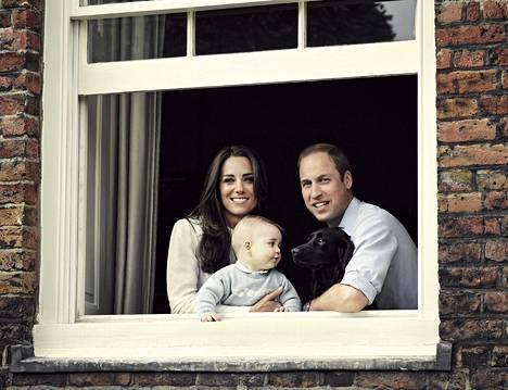 Prinssi William, Catherine, prinssi George ja Lupo-koira poseerasivat Kensingtonin palatsin ikkunassa maaliskuussa 2014.