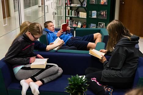 Ronja Lehti (vas.), Ilkka Miettinen ja Onerva Pirttimaa syventyivät lukemaan Tapiolan koulun kirjastossa.