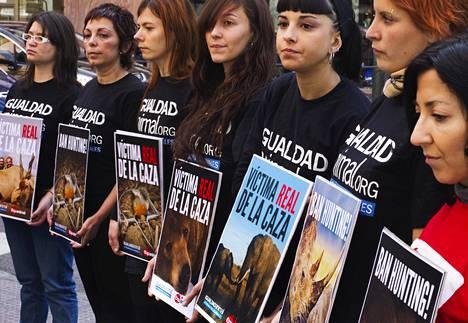 """Eläinoikeusaktivistit osoittivat mieltään sairaalan ulkopuolella Madridissa huhtikuussa 2012 kuningas Juan Carlosin murrettua lonkkansa norsunmetsästysretkellä Botswanassa. Espanjankielinen sana """"real"""" voi tarkoittaa sekä todellista että kuninkaallista, joten aktivistien pitelemien kylttien tekstit voi lukea joko """"metsästyksen todelliset uhrit"""" tai """"metsästyksen kuninkaalliset uhrit""""."""
