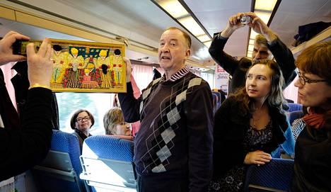 Mielenterveyshoitaja Ilkka Raitasuo kertoi junamatkalla Anna Lappalaisen värikkäästä elämästä. Hän näytti myös Lappalaisen tekemän taulun. Matkalla mukana olivat muiden muassa Hanna-Kaisa Mettälä (vas.) ja Raija Kivimetsä Espoosta.