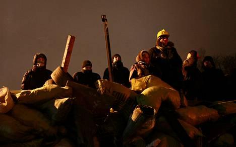 Mielenosoittajat tähyilivät poliiseja barrikadiensa takaa Kiovan keskustassa torstaina.