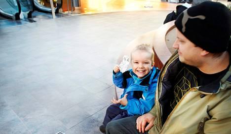 """Mika Aalto, 36, ja Vili-Benjamin Aalto, 3, kävelivät tällä kertaa Jumboon ruokaostoksille. He käyvät marketeissa myös autolla, vaikka matkaa on alle viisi minuuttia. Vili-Benjamin nappasi punnituslappuja tuliaiseksi äidille. """"Tämä on ystävänpäivälahja."""" Äidin kanssa Vili-Benjamin käy usein perjantaisin Jumbossa jäätelöllä."""