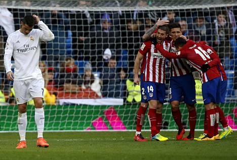 Real Madridin Cristiano Ronaldo raapi päätään, kun Atléticon pelaajat juhlivat päätösvihellyksen jälkeen.