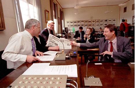 Keskustan eduskuntaryhmän puheenjohtaja Aapo Saari (vas.) ja kansanedustaja Kauko Juhantalo tutkivat päivän lehteä ryhmäkokouksessa maaliskuussa 1995. Taustalla Annikki Koistinen ja Matti Vanhanen.