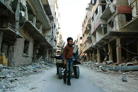 Poika kuljetti raunioista keräämiään tavaroita Doumassa maanantaina.