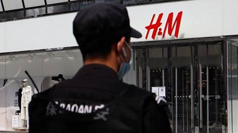Turvamies tarkkaili tilannetta Pekingissä sijaitsevan H&M-vaatekaupan edustalla torstaina.