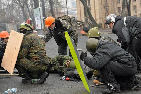 Mielenosoittajat tutkivat tarkka-ampujan luodeista haavoittunutta toveriaan Kiovassa 20. helmikuuta.