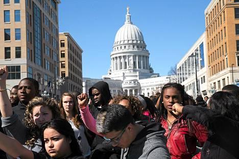Koulupäivänsä keskeyttäneet mielenosoittajat huusivat iskulauseitaan Madisonissa, Wisconsisissa maanantaina.