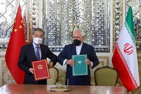Kiinan ja Iranin ulkoministerit Wang Yi (vas.) ja Mohammad Javad Zarif tekivät kyynärpäätervehdyksen allekirjoitettuaan yhteistyösopimuksen Teheranissa lauantaina.