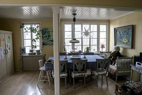 Aulikki ja Väinö-koira Kallahdenniemen huvilan keittiössä. Seinillä on Yngve Bäckin taidetta.